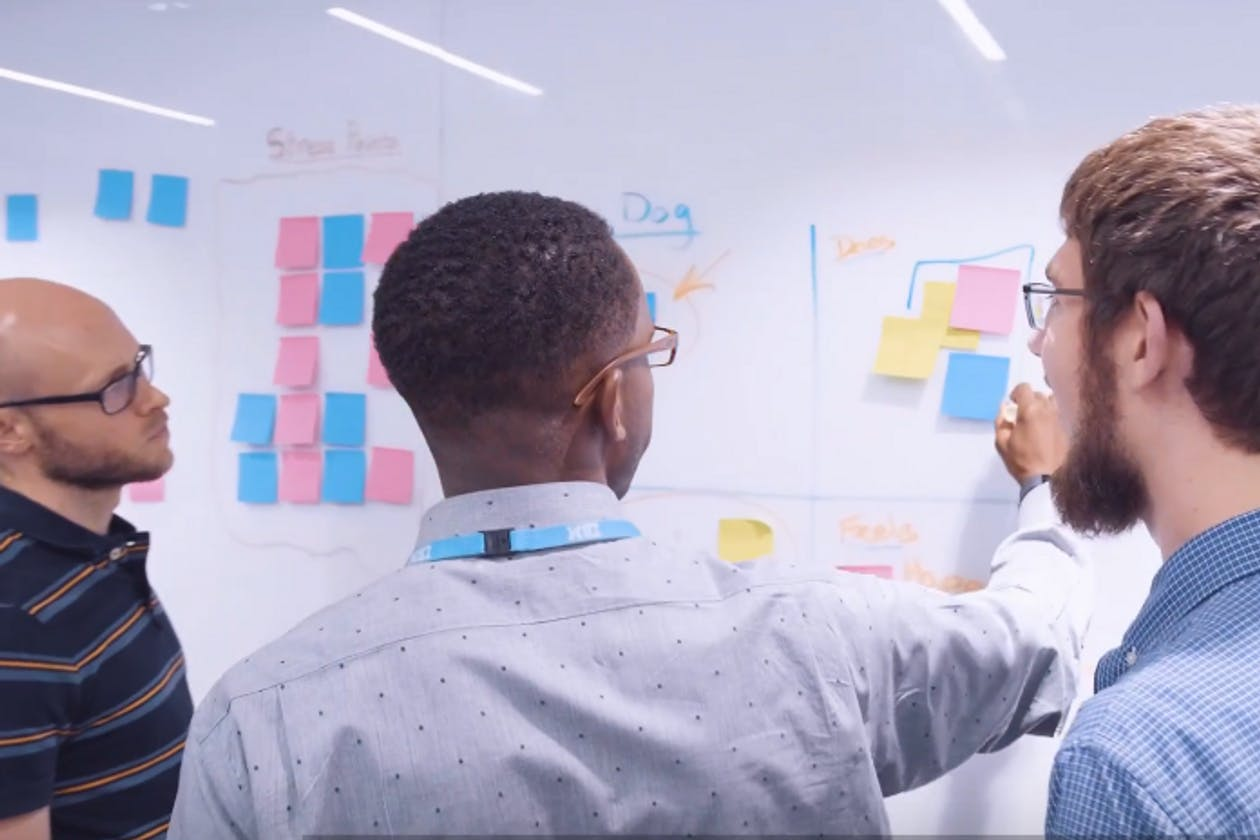Three men working at a whiteboard using markers and post-it notes
