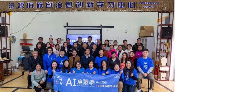 A group picture. The front row is holding a banner for IBM volunteers and the AI Enlightment season