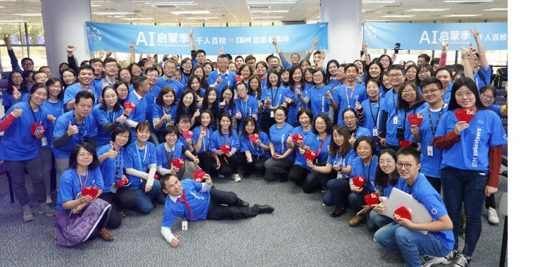 A large group of IBM volunteers in China under banner for the AI Enlightenment Season