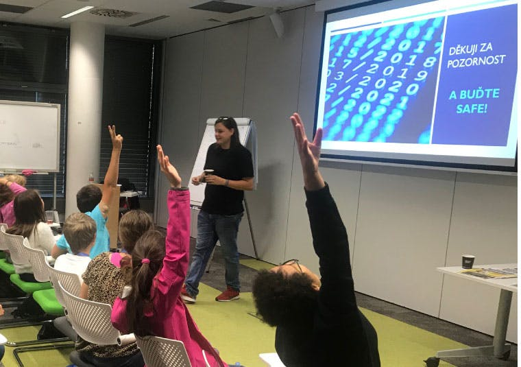 An IBM volunteer in front of an audience of children with their hands raised to answer a question