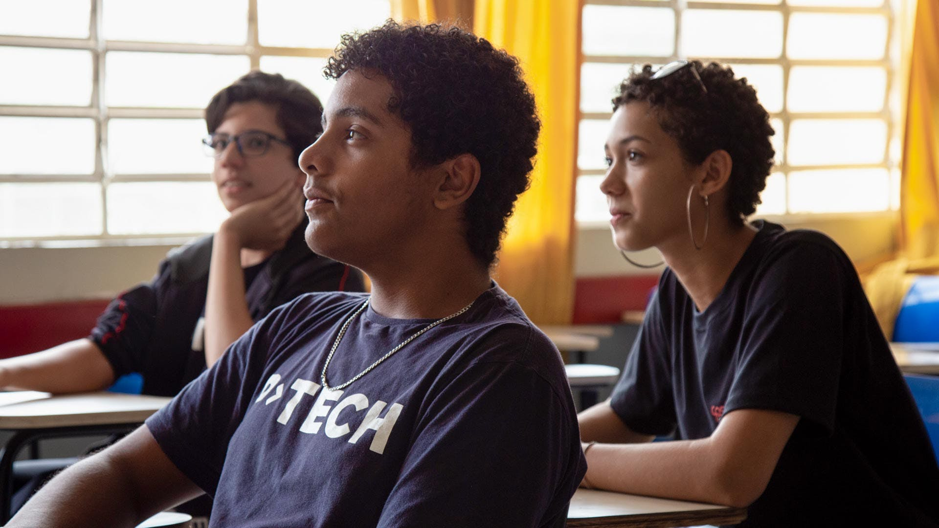 Three high school students in a P-TECH classroom in Brazil