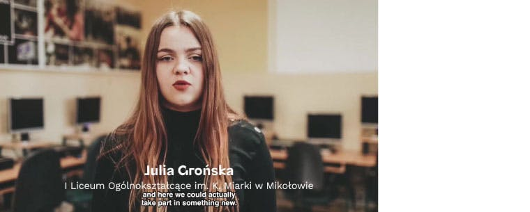 A photo of a P-TECH student, Julia Gronska, from a video. The subtitles on the screen are in Polish and English, and read: and here we could actually take part in something new. are in Polis