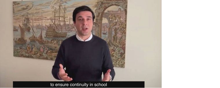 """A screenshot taken from a video of a man in front of painting of an Italian river scene. The subtitle at the bottom of the screen shot reads, """"to ensure continuity in school"""""""