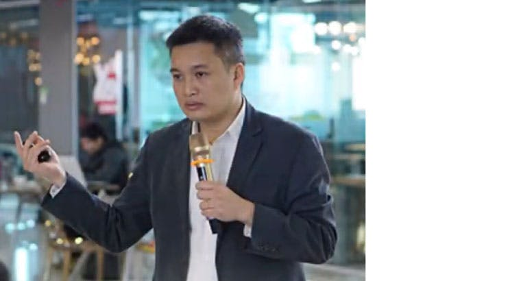 Le Nhan Tam speaking with a microphone