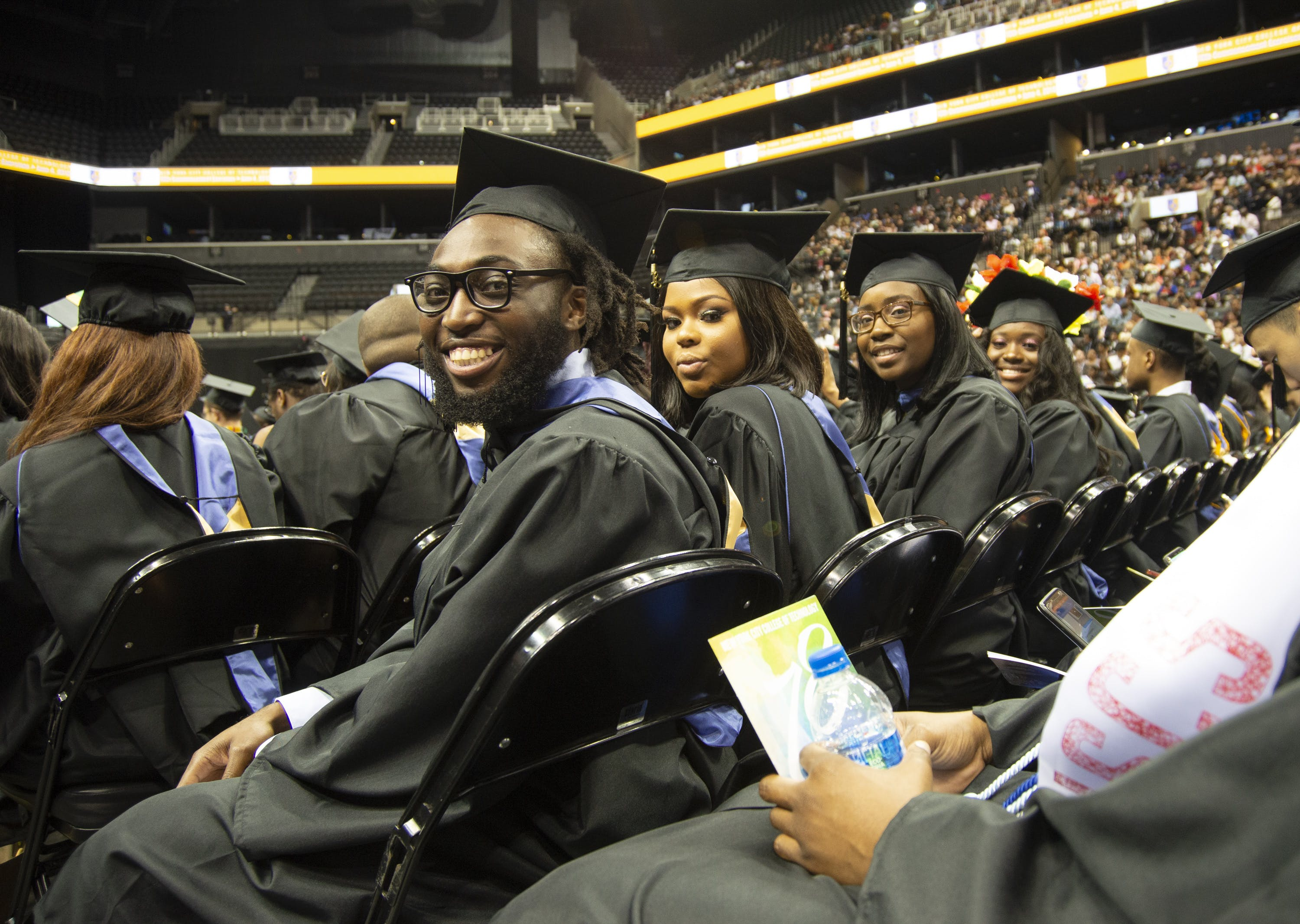 Students in caps and gowns sitting in a row at graduation
