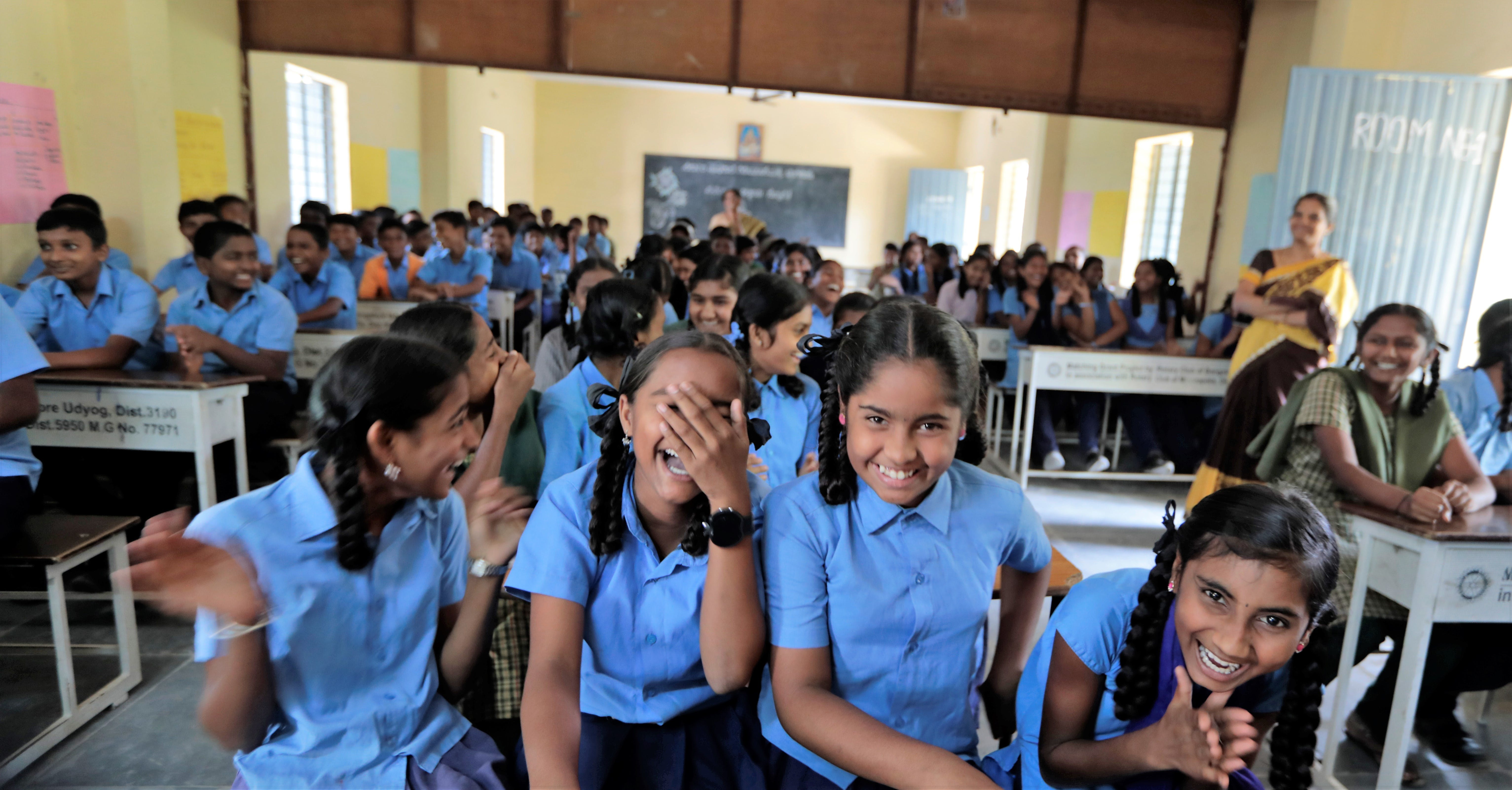 Young girls smiling and laughing in a classroom in India