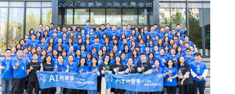A very large group of people arranged in rows on steps. Most are wearing blue t-shirt with the pictogram of an eye, a bee and the letter M. The front row holds two banners reading IBM volunteers and AI Enlightenment Season