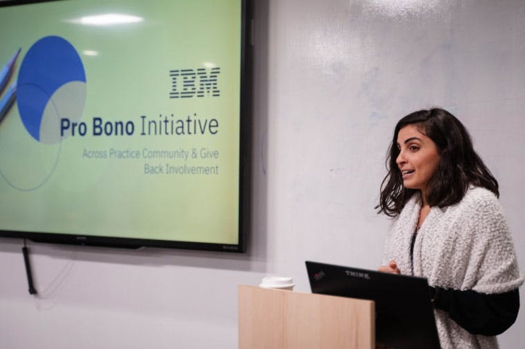 "A woman speaks from behind a lecture, the screen beside her reads ""IBM Pro Bono Initiative, Across Practice Community & Give Back Involvement"
