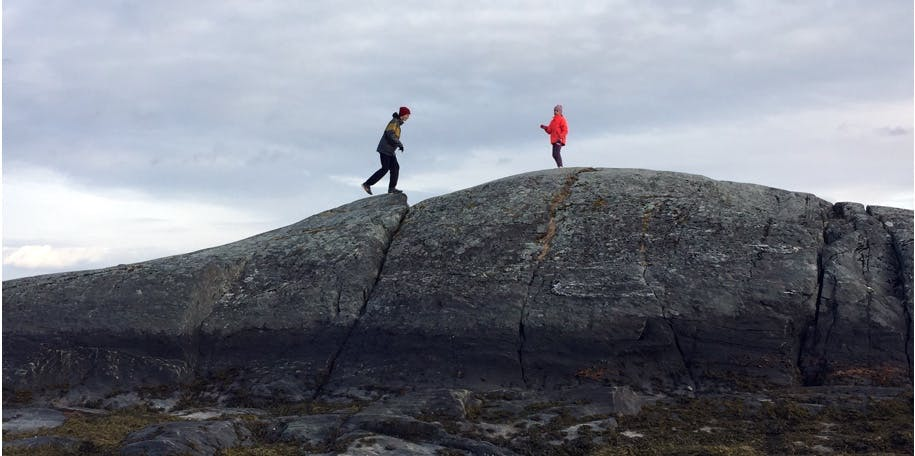 People hiking on a large rock