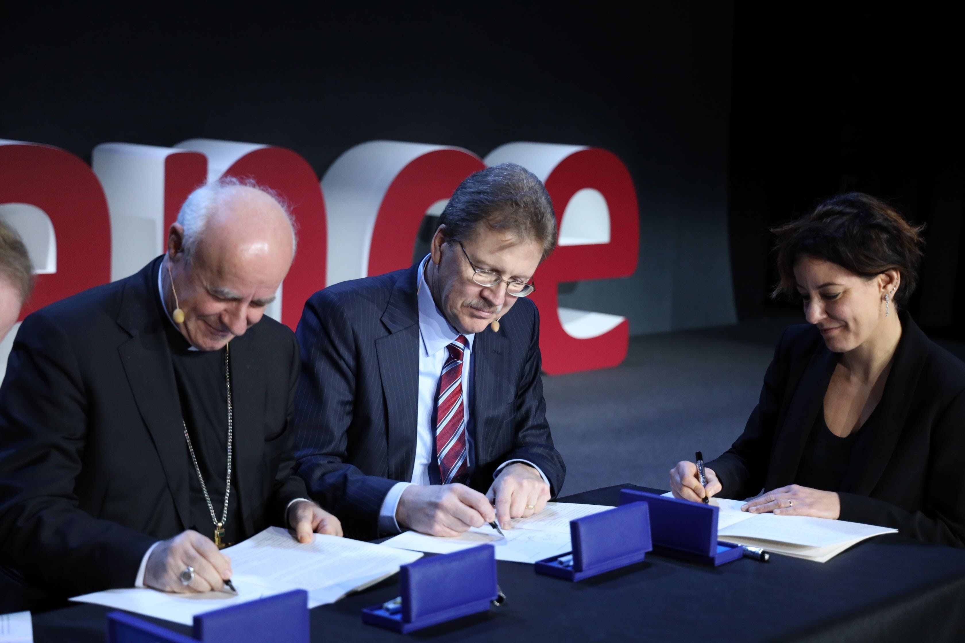 Two men and a woman signing the Rome Call for Ethics
