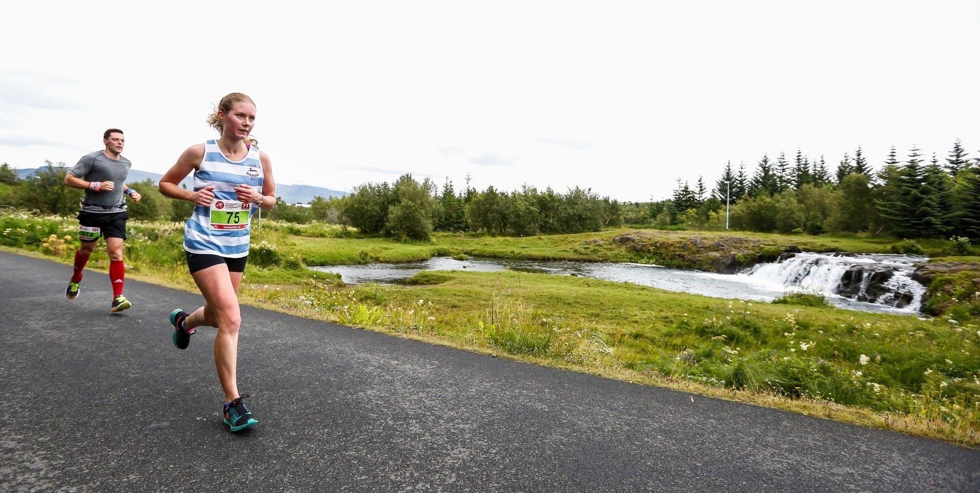 Mynd úr Reykjavíkurmaraþoni af konu & manni að hlaupa meðfram fossi