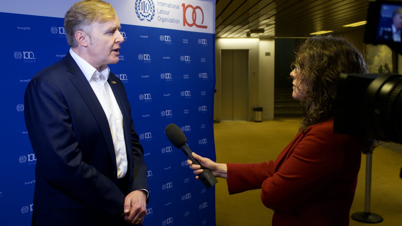 LinkedIn Co-Founder Allen Blue at ILO Headquarters in Geneva gives an interview to a women with a microphone.