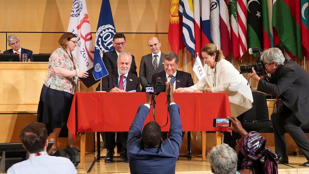 Le Directeur Général de l'OIT et le Président de la CIT 2019 sur une scène, signant la Déclaration du centenaire de l'OIT sur l'Avenir du Travail lors de la Conférence Internationale du Travail à Genève en juin 2019.