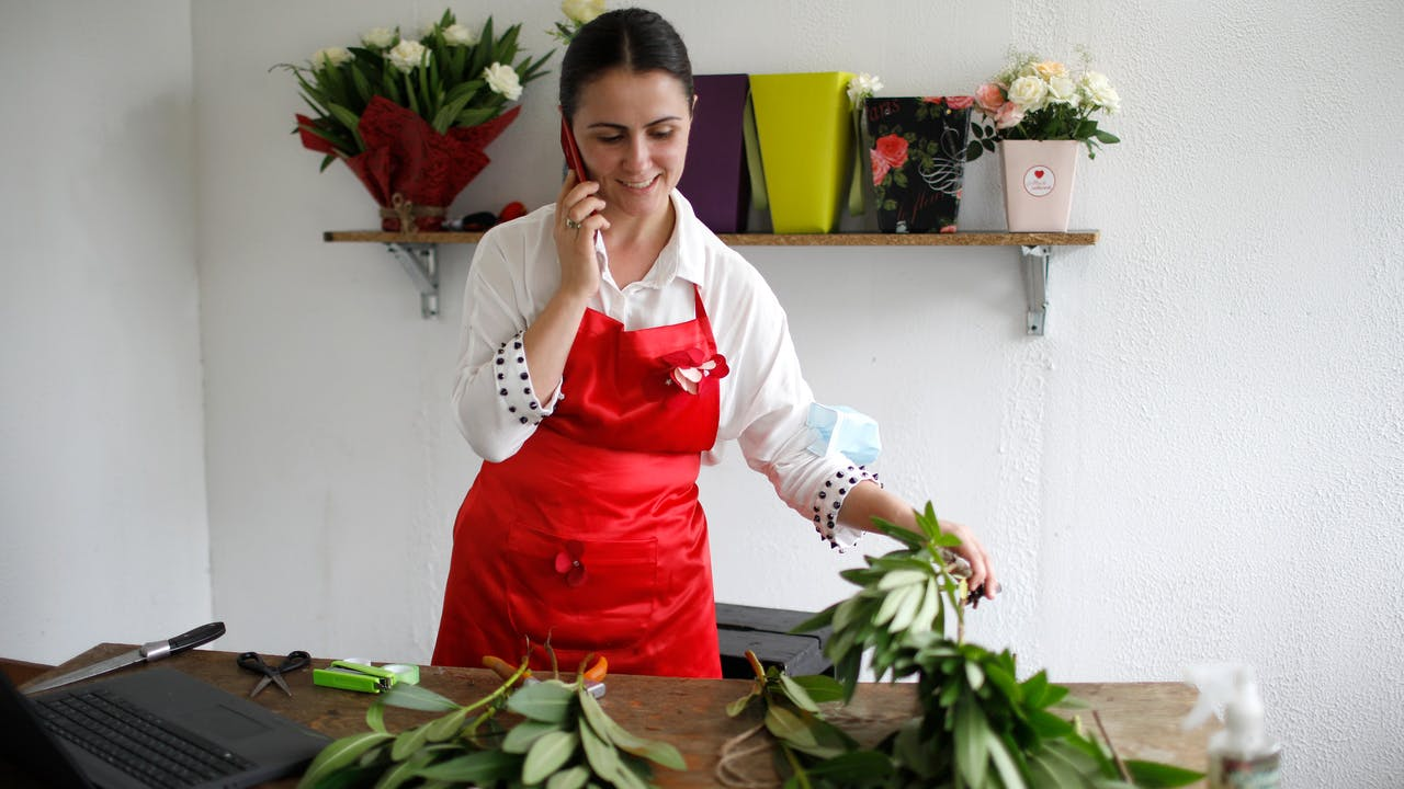 Mariam Kobalia stands in her flower shop, holds her phone in one hand and a flower in the other.   In the foreground on the table there are cut flowers and a laptop.