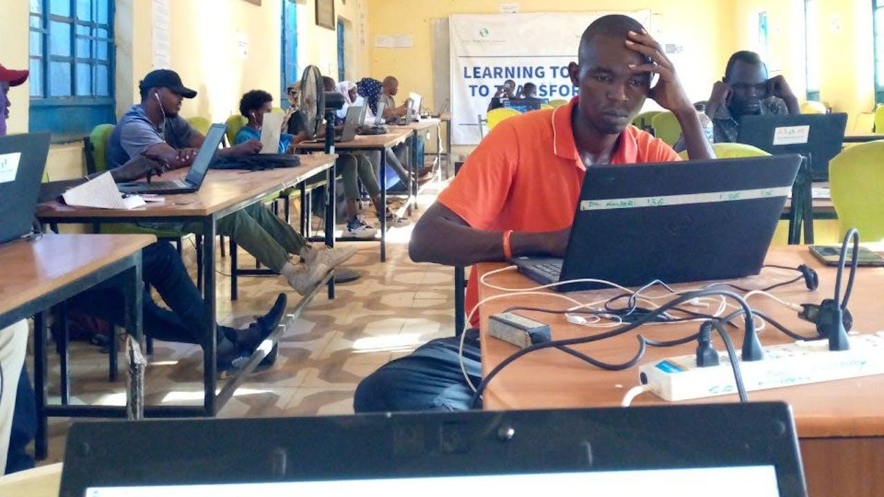 Varios jóvenes miran la pantalla de ordenadores portátiles en el centro de Internet del campo de refugiados de Kakuma, en Kenia.