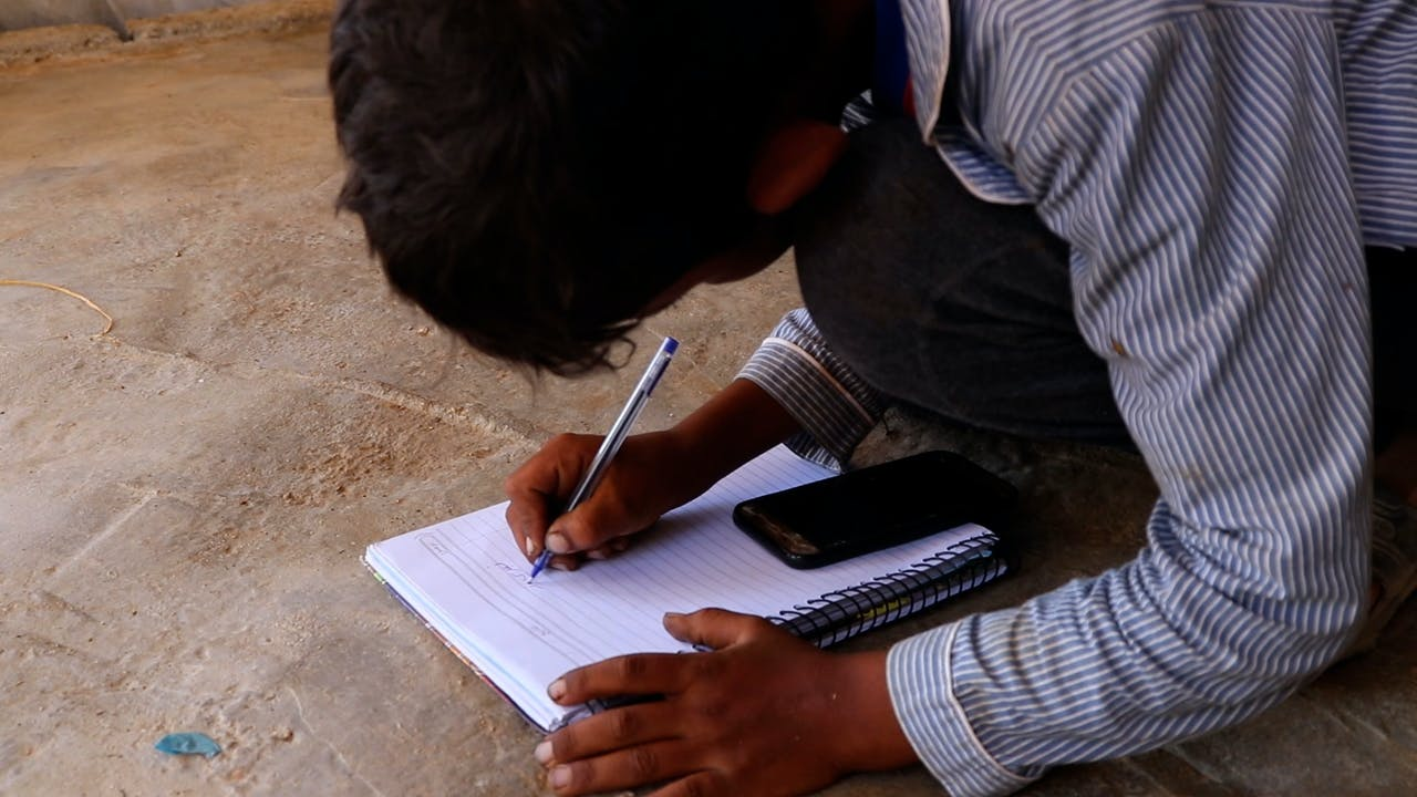 Fatima's son is crouched over a mobile phone and writes in his school notebook.