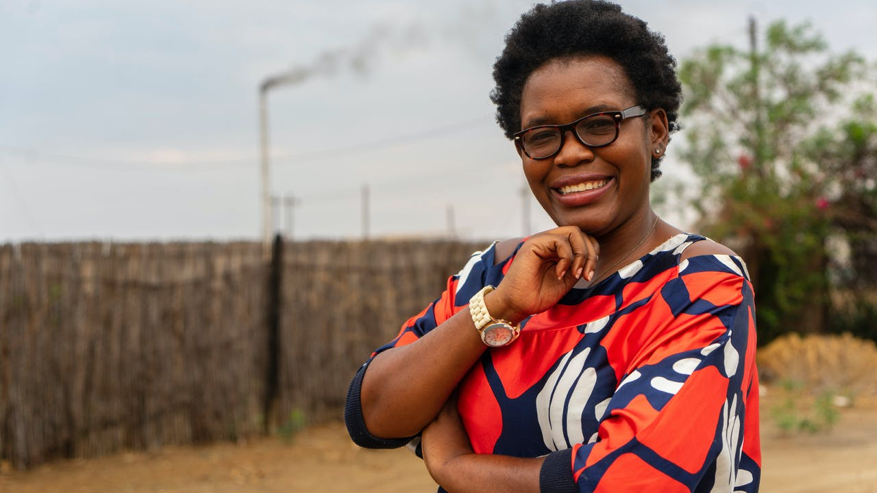 Portrait of Mendy Lerato Lusaba in bright orange, blue and white shirt.