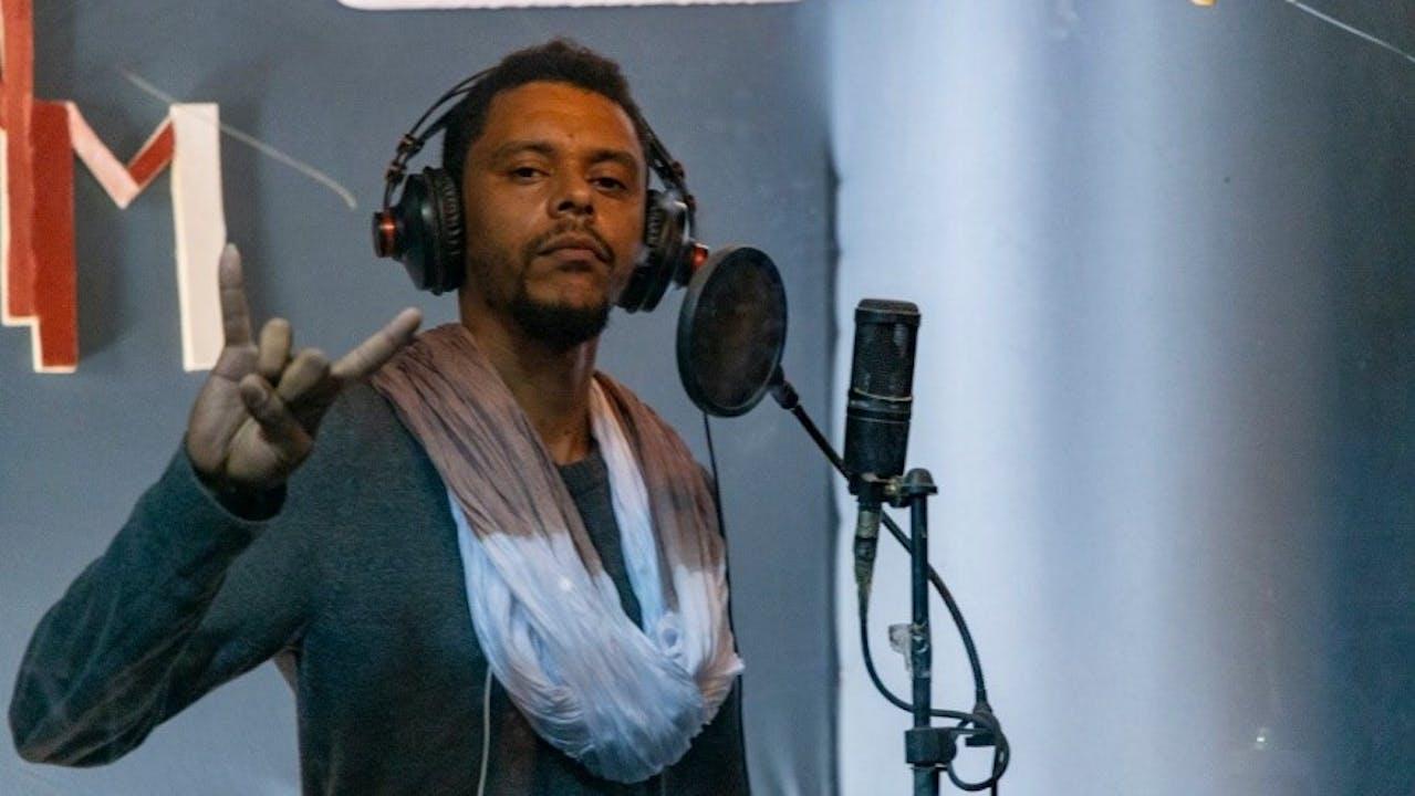 Le rappeur Mauritanien «Le Baron» se tient devant un micro dans un studio. Avec sa main droite, il fait le signe de Rock'n Roll.
