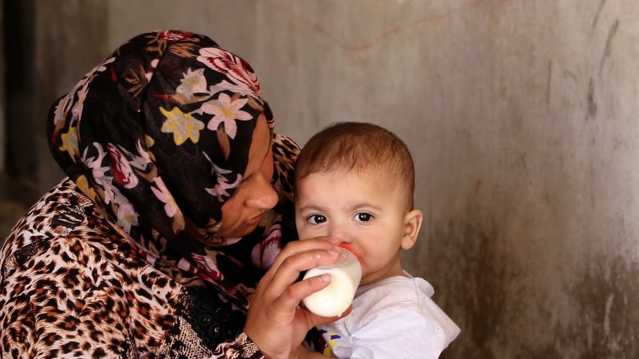 Fatima feeds her baby daughter with a bottle of milk.