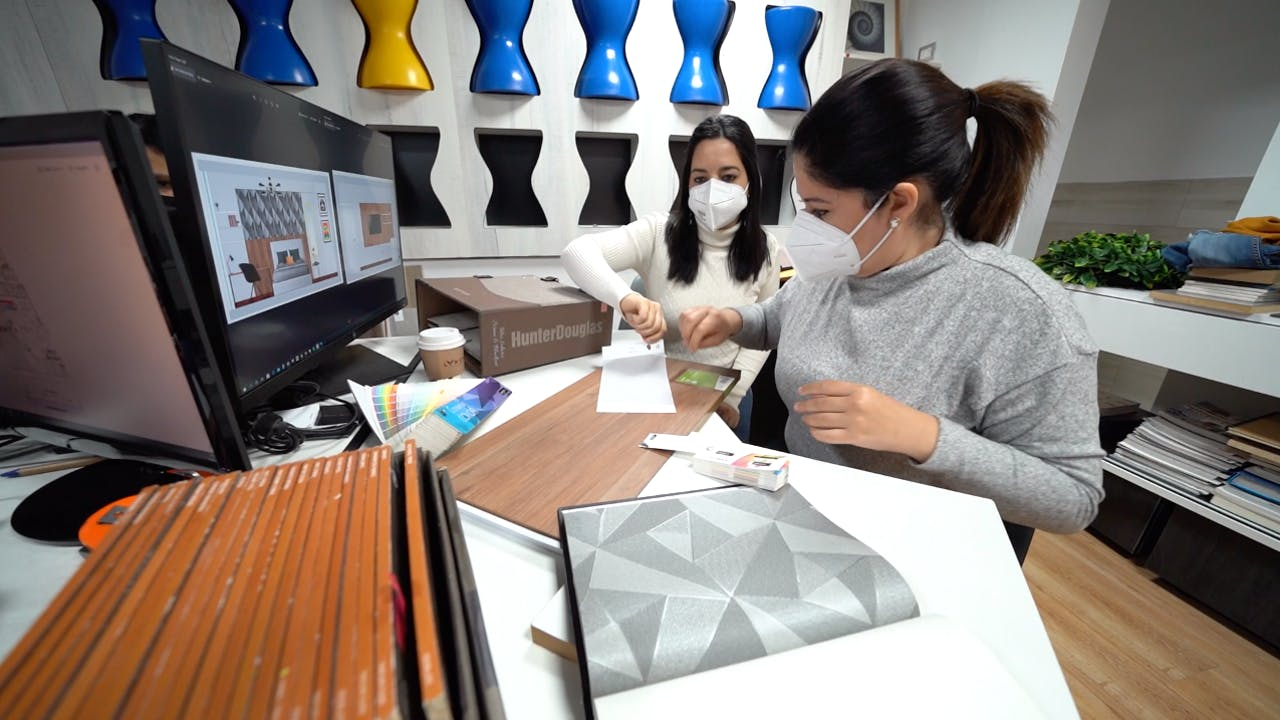 Women architects work in an office with face masks.