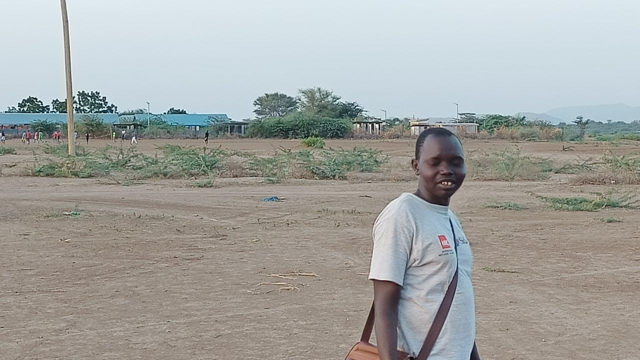 Thon de pie, con un árido paisaje con poca vegetación y edificios del campamento de Kakuma al fondo.