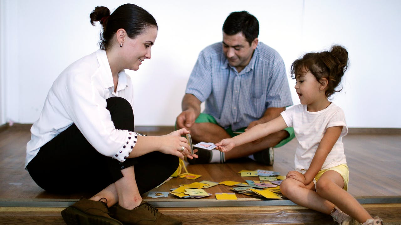 Mariam Kobalia plays a card game with her four-year-old daughter and her husband.