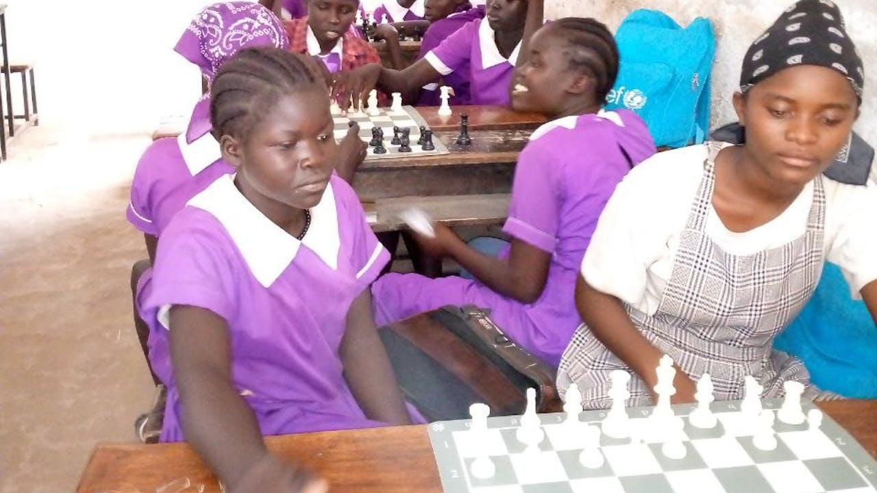 Varias niñas con uniforme escolar de color púrpura juegan al ajedrez.