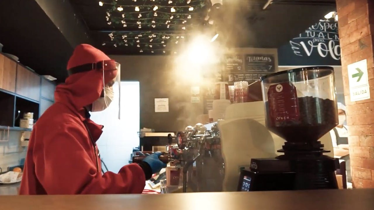 One of the employees prepares coffee and wears personal protective equipment and clothing  to avoid contagion.