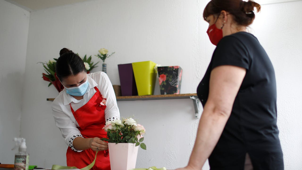 Mariam Kobalia prepares white roses in a vase for a customer.  Both Mariam and the customer wear a mask.