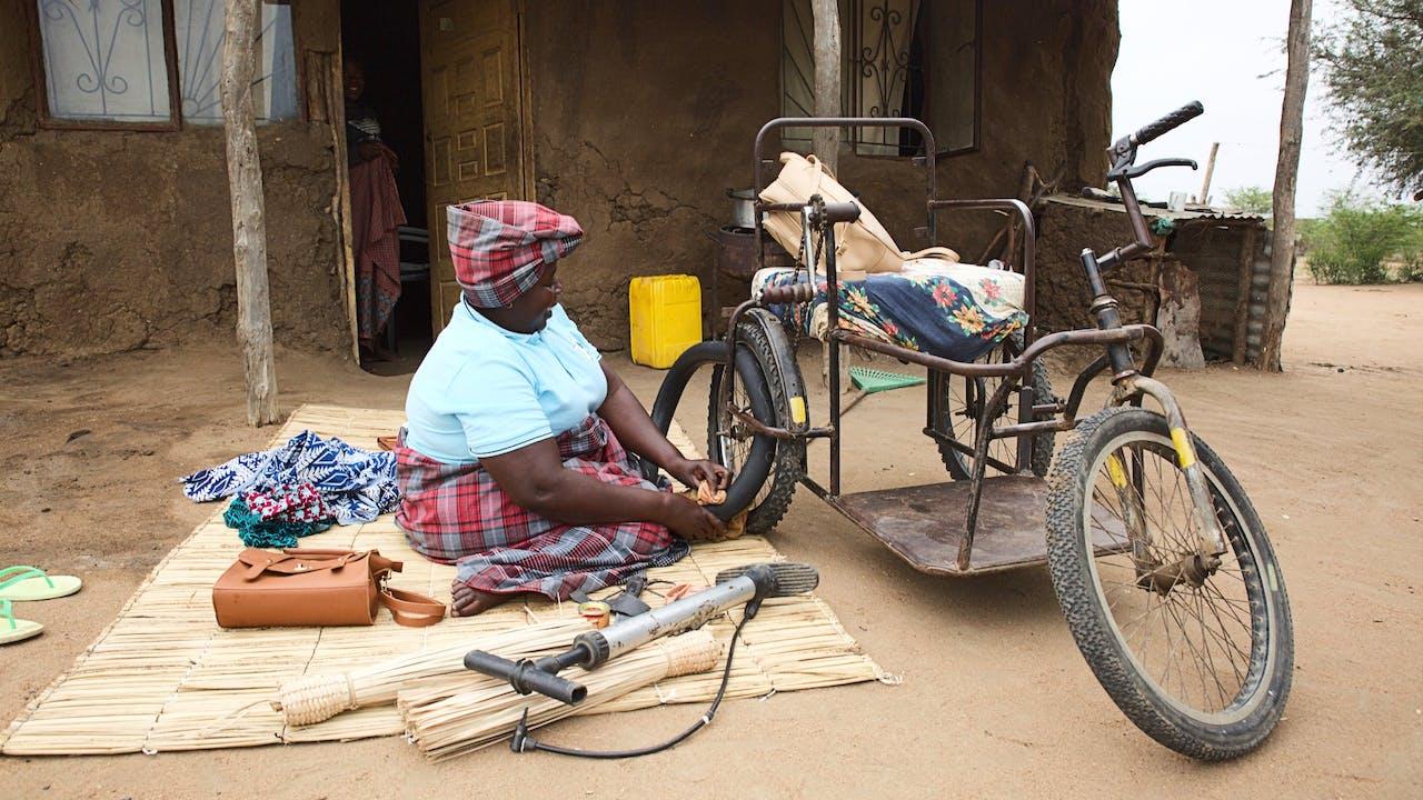 Linda Sarmento est assise par terre, à l'extérieur de sa maison et répare un trou dans la chambre à air d'une des roues de son fauteuil roulant.