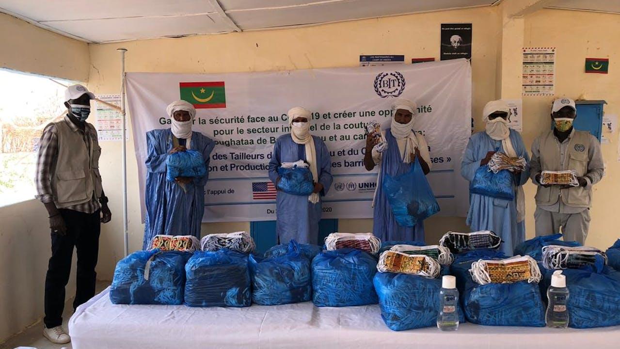 Six hommes qui portent des masques sont debout derrière une table remplie de masques dans des sacs en plastique bleu.  Il y a un panneau derrière eux avec le nom du projet de l'OIT, le logo de l'OIT, le drapeau de la Mauritanie, et le drapeau des Etats-Unis, qui soutient le projet de l'OIT et du UNHCR.