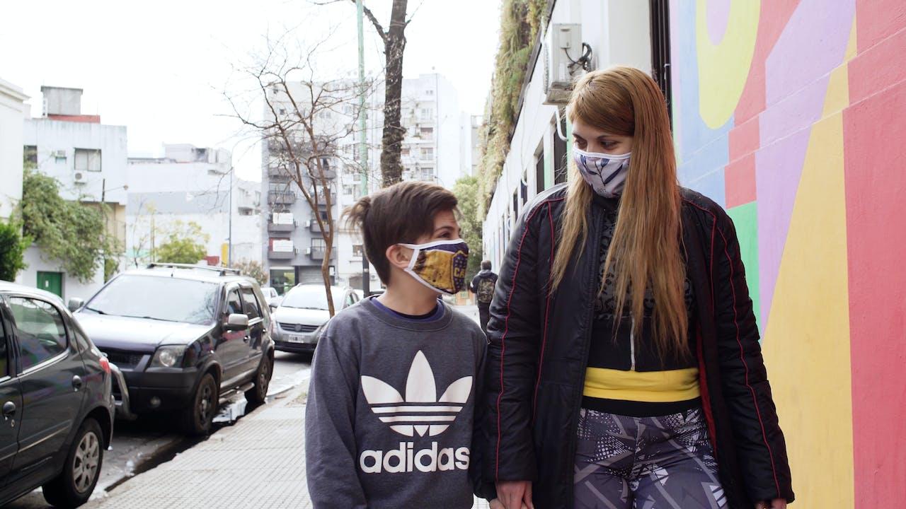 María Belén Fierro se promène dans la rue à côté de son fils, tous deux portant des masques.