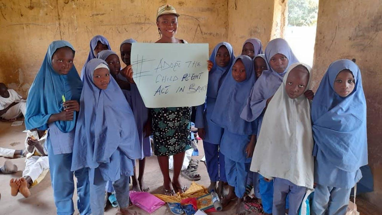 """Peace Okebugwu, trabajadora de una ONG, sostiene un cartel que dice """"#Apruebe la ley sobre derechos infantiles en Bauchi"""", rodeada de alumnas con pañuelos azules y uniforme. Algunos niños descansan sentados en el suelo. Cabaña escolar rudimentaria."""