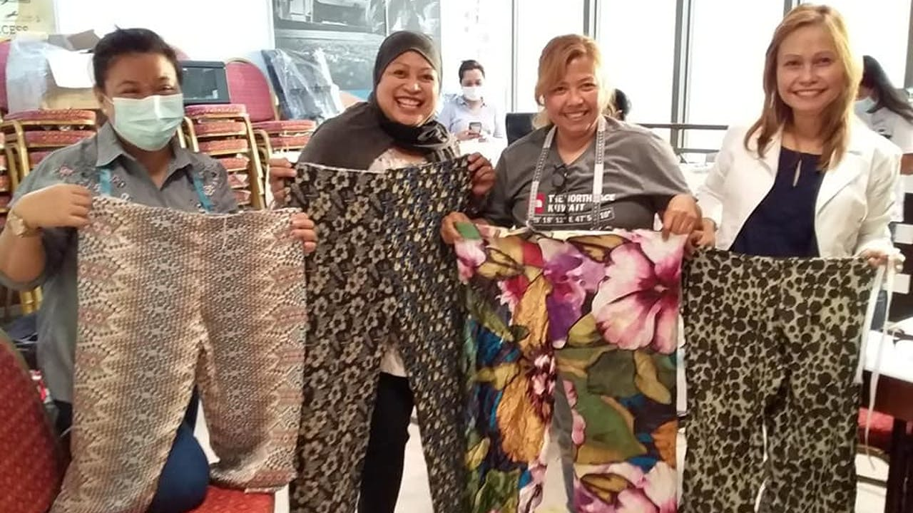 Domestic workers show off the trousers they have made at the sewing livelihood training run by Sandigan.