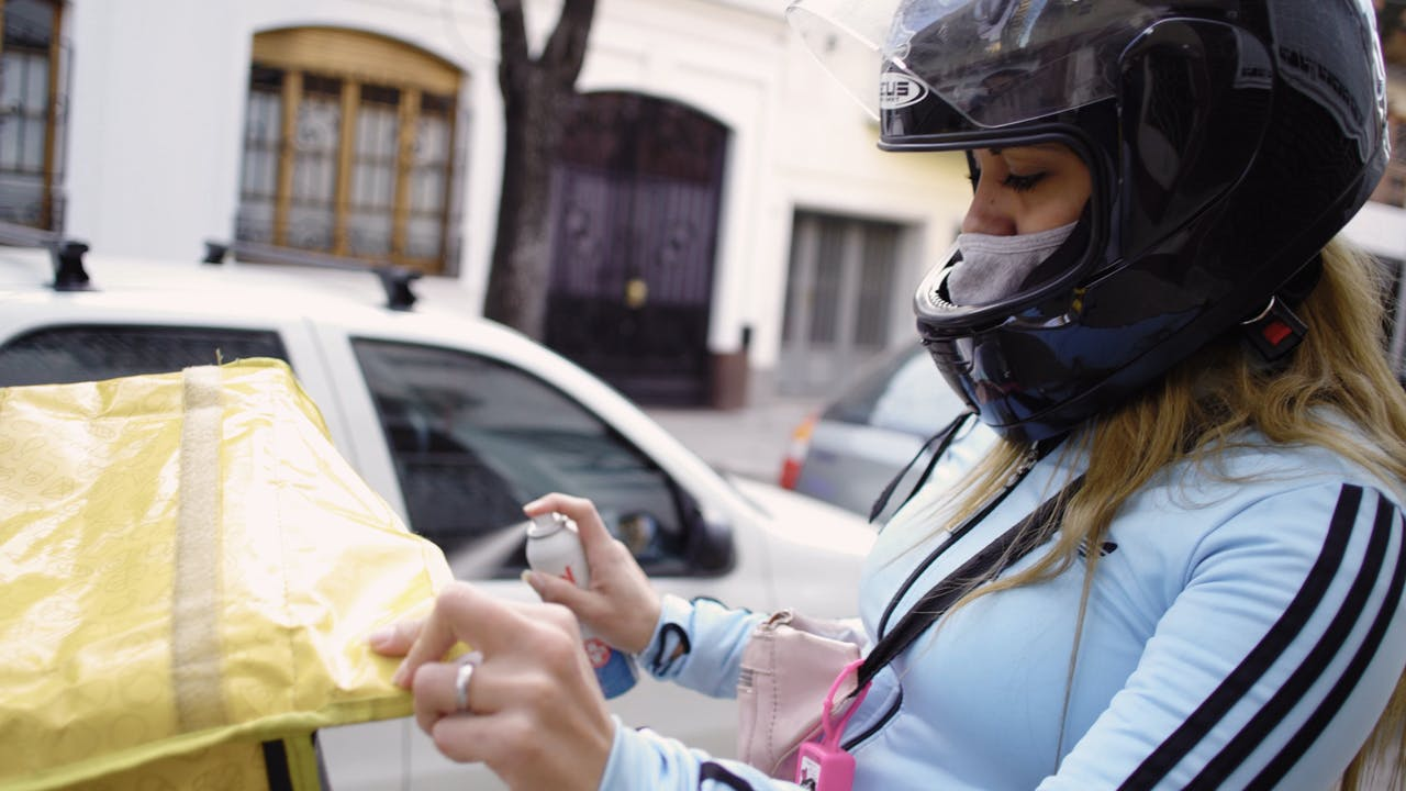 María Belén Fierro disinfects her motorbike after a delivery