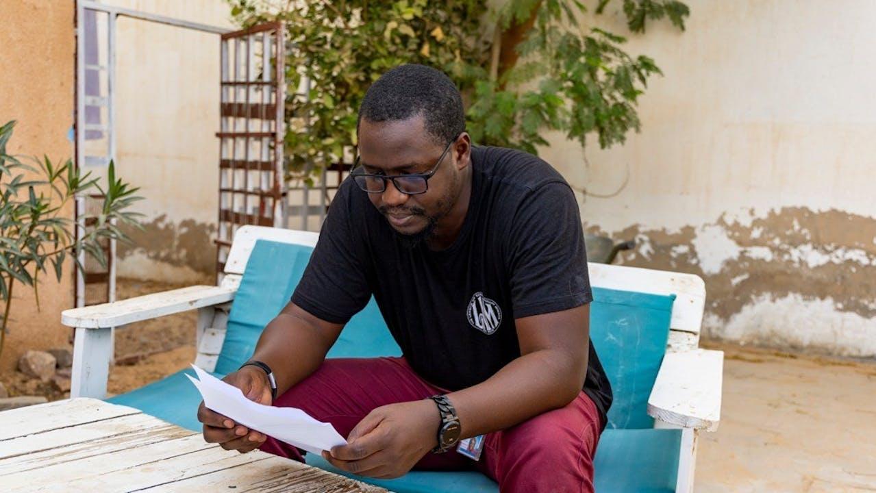 Seyidina Alioune Diallo assis à l'extérieur en train d'apprendre les paroles de la chanson de rap.