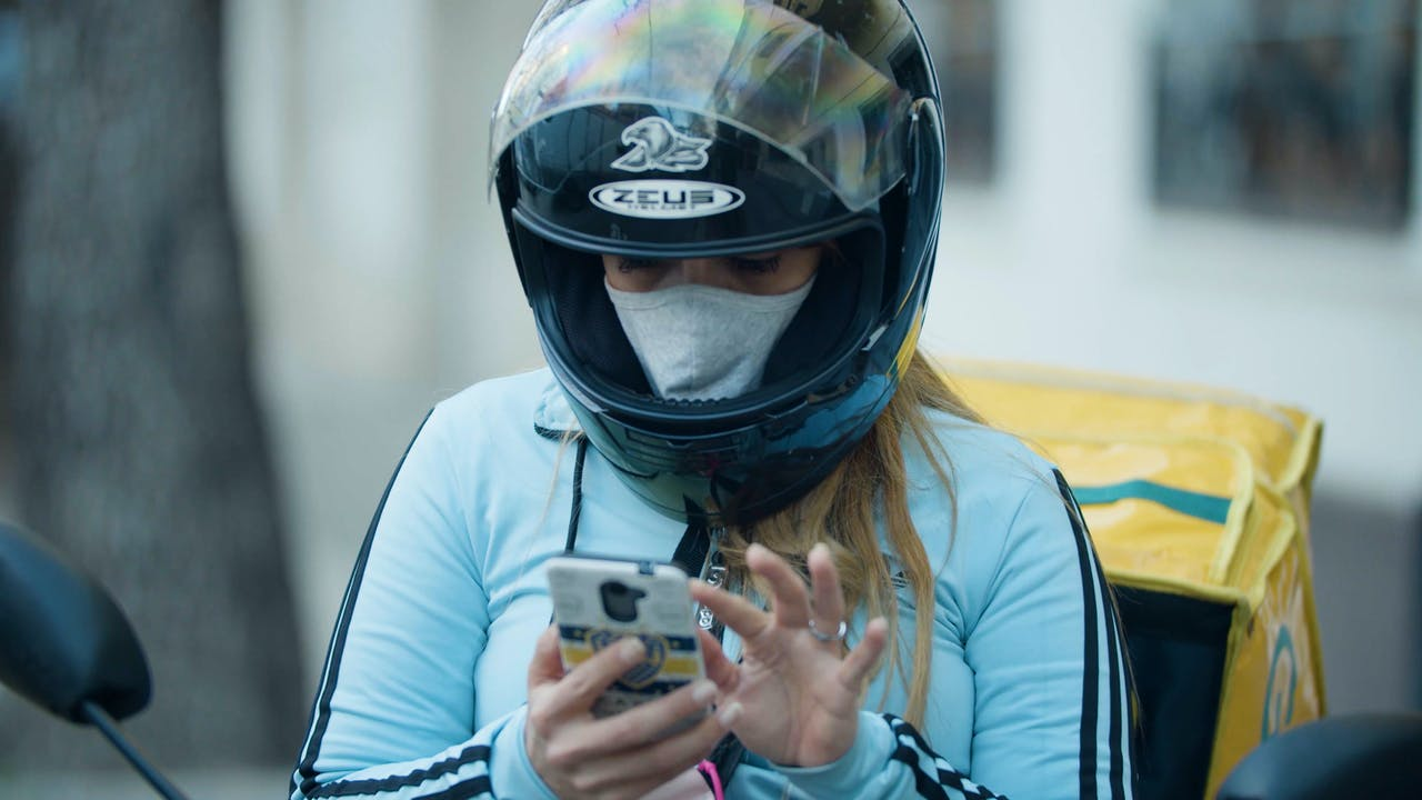 María Belén Fierro's sits on her motorbike checking her phone