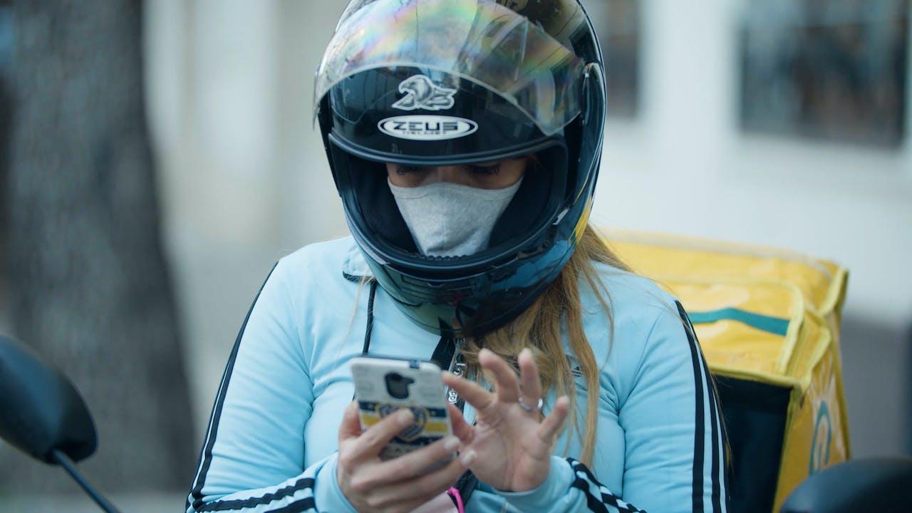 María Belén Fierro est assise sur sa moto et regarde son téléphone