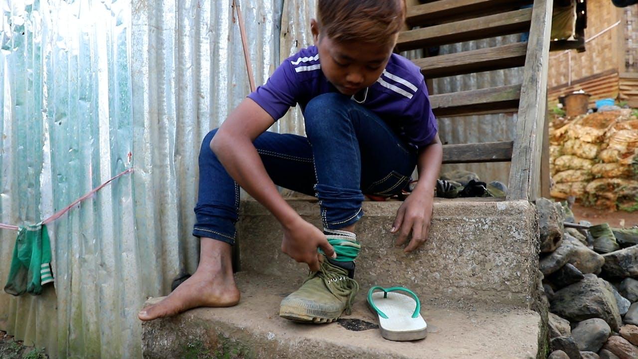 Min Min se pone los zapatos mientras se prepara para ir buscar piedras de jade.