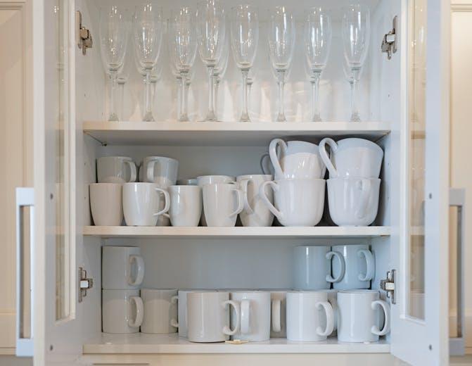 canecas e copos de champanhe em armário de cozinha organizado