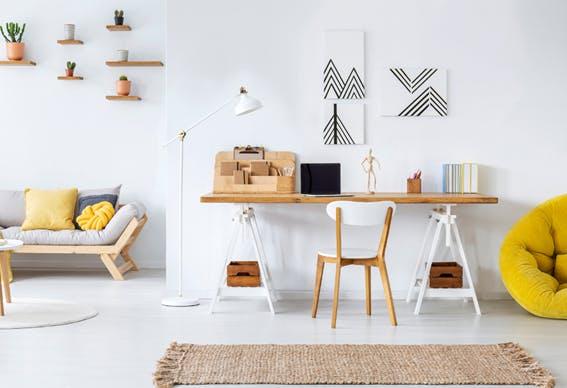 escritório em casa decorado com cores claras, quadros e com arrumação