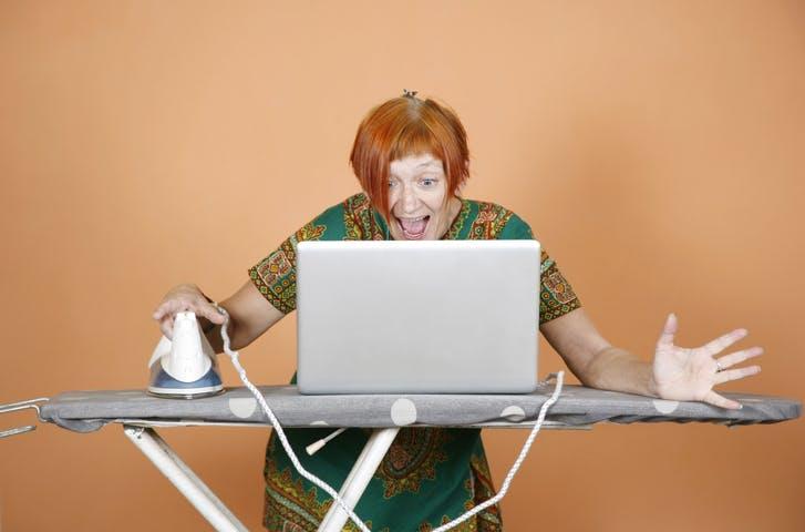 mulher em casa com tábua de engomar e computador