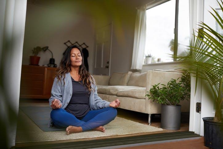 mulher a praticar yoga na sua sala de estar