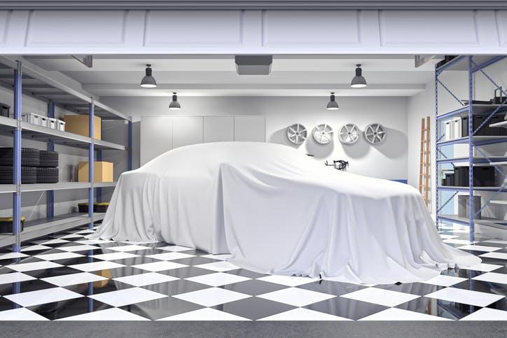 garagem com carro tapado e prateleiras de arrumação