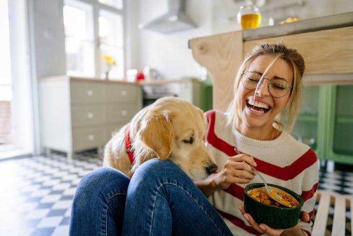 mulher a tomar o pequeno-almoço com o cão