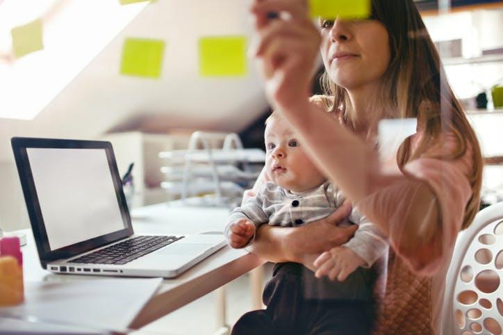 mulher com bebé ao colo a trabalhar