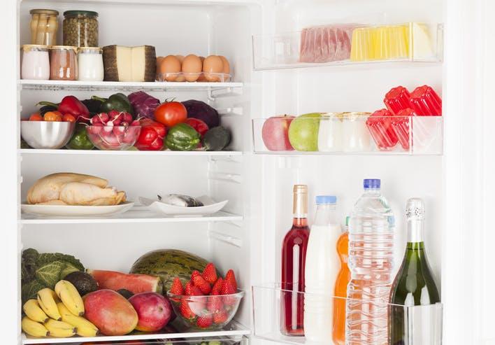 frigorífico aberto com frutas, legumes e iogurtes