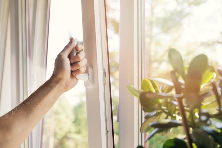 mão de uma pessoa a abrir a janela para entrar luz e ar