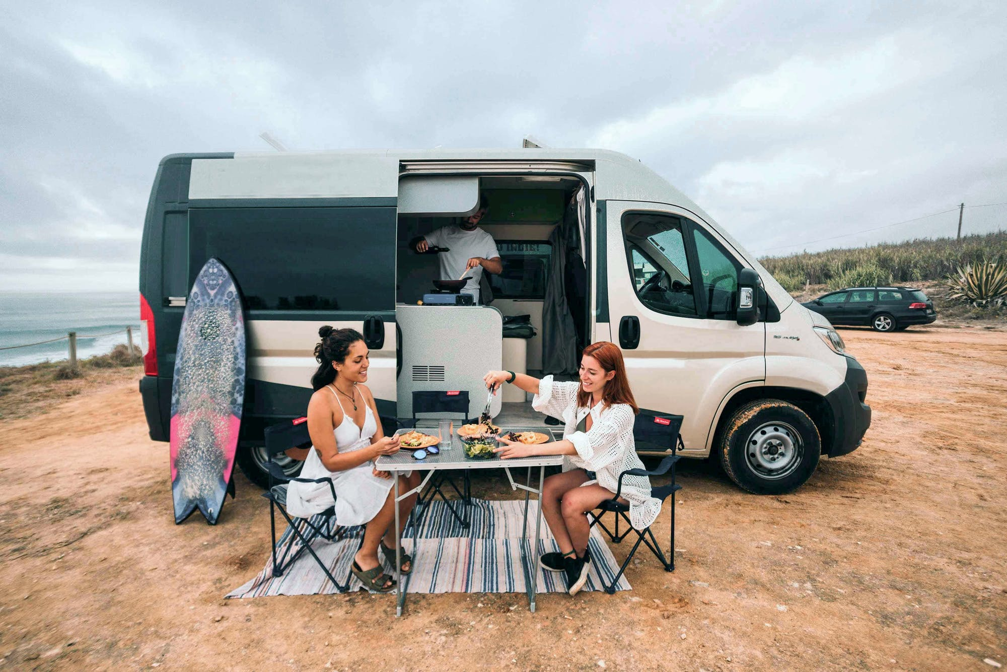 Friends doing a picnic outside the campervan Active Model from Indie Campers