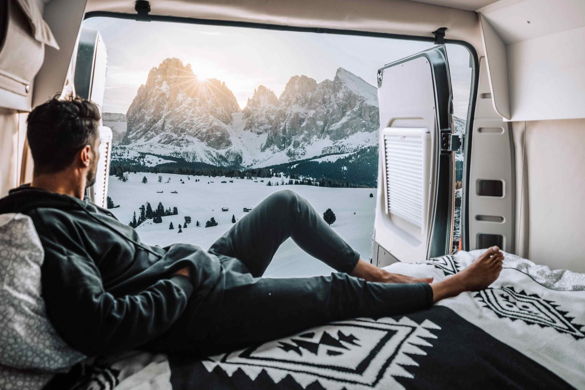 Man observing snowy mountains from the Nomad Model's inside